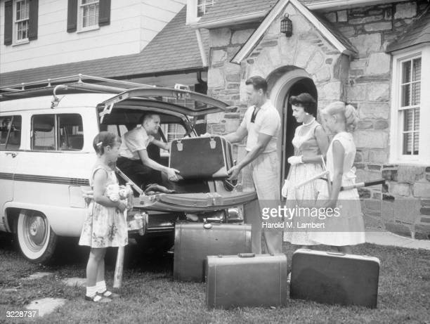 A young boy helps his father pack a suitcase into the back of the family's Ford Country Squire station wagon in preparation for a vacation as the...