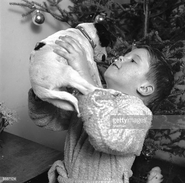 A young boy holding his puppy