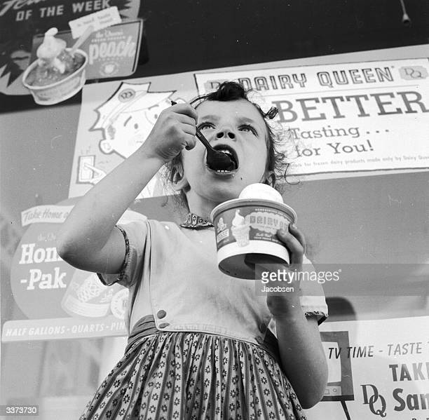 A young girl eating ice cream outside a Dairy Queen store