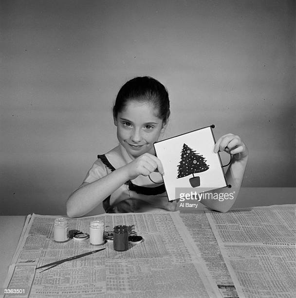 A young girl holds up a coffee pot mat which she has decorated with a Christmas tree