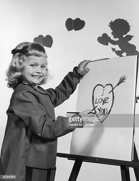 A young girl paints 'I Love You' in the center of a heart on paper at an easel Valentine's Day cutouts of hearts and cupid decorate the back wall