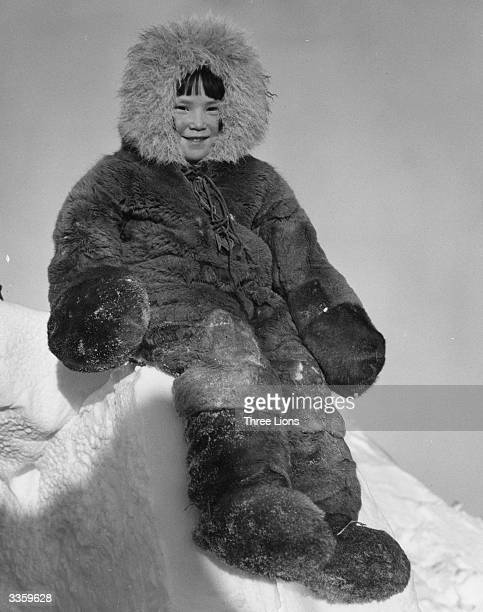 A young Inuit girl wearing traditional winter clothing