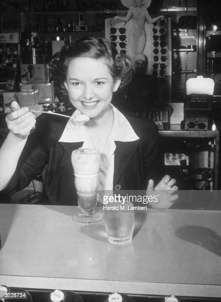A young woman smiles as she prepares to have a spoonful of an ice cream soda while sitting at a soda fountain counter