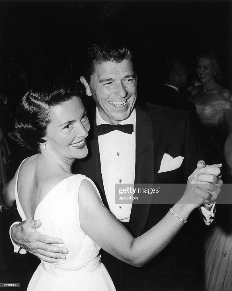 American actor and politician Ronald Reagan smiling and dancing with his wife Nancy at a charity party Reagan is dressed in a tuxedo His wife is...