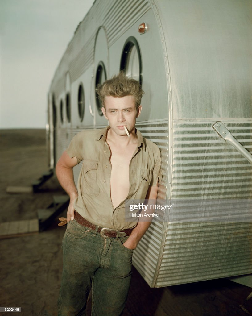 American actor James Dean leaning against a dressing room trailer with his shirt open to the waist while smoking a cigarette on the set of director...