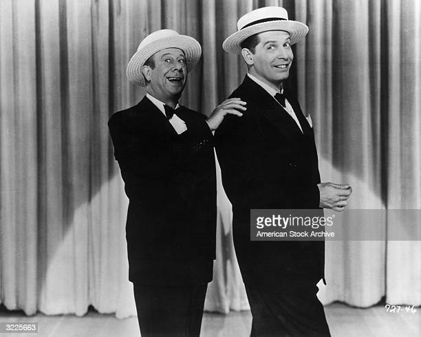 American actors and comedians Bert Lahr and Milton Berle smile while performing on stage together in tuxedos and straw hats