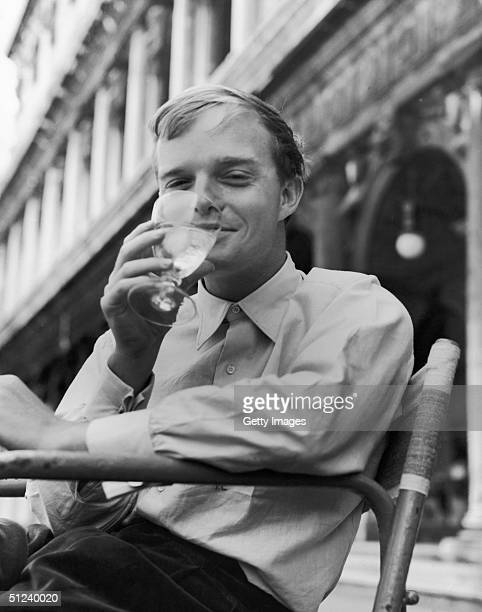 Circa 1955 American author Truman Capote smiles as he drinks a glass of ice water at an outdoor cafe in San Marco's Square Venice Italy 1950s