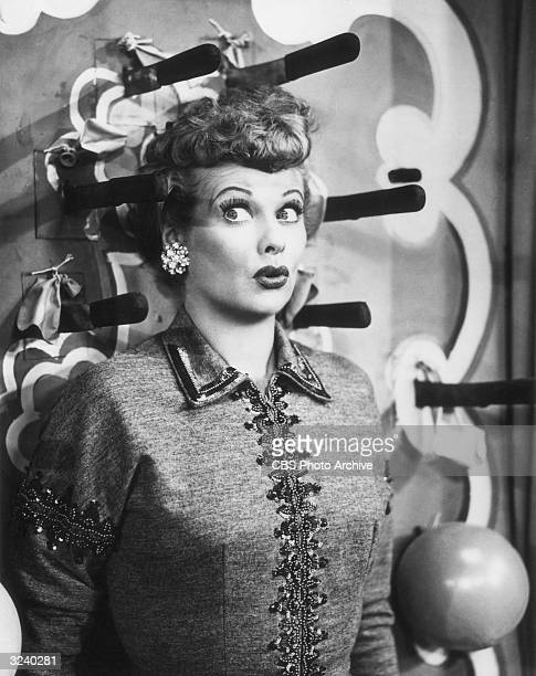 American comedian and actor Lucille Ball looks surprised as she stands against a wall as a knife thrower's target surrounded by knives in a still...