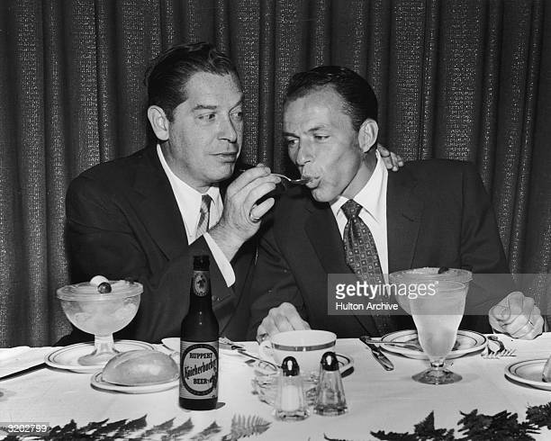 American comedian Milton Berle feeds singer and actor Frank Sinatra with a spoon while sitting with fruit cocktail cups in front of them at a banquet...