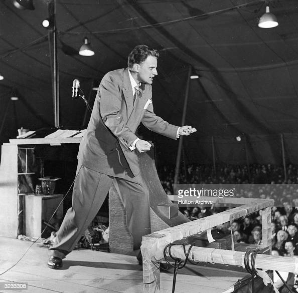 American Evangelist preacher Billy Graham walks across the stage and clenches his fists while preaching in a tent 1955 The Rev Graham an ordained...