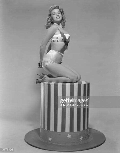 American film star Jayne Mansfield sitting on top of a large scale model of Uncle Sam's hat wearing a bikini