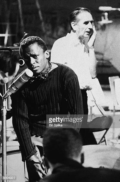 American jazz trumpeter Miles Davis talking into a micophone as Canadian arranger Gil Evans stands behind him in a recording studio during one of...