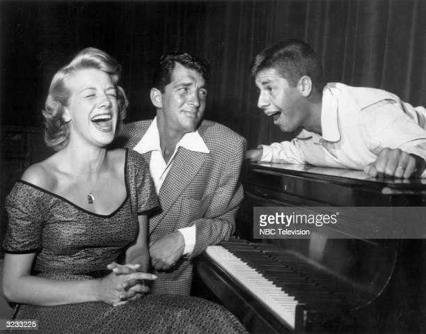 American singer and actor Rosemary Clooney sits on a piano bench next to singer and actor Dean Martin as comedian Jerry Lewis lies on top of the...