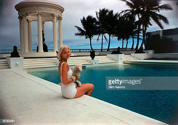 American socialite Mrs Winston F C Guest perches on the edge of the Grecian temple pool on her oceanfront estate Villa Artemis Palm Beach Florida 1955