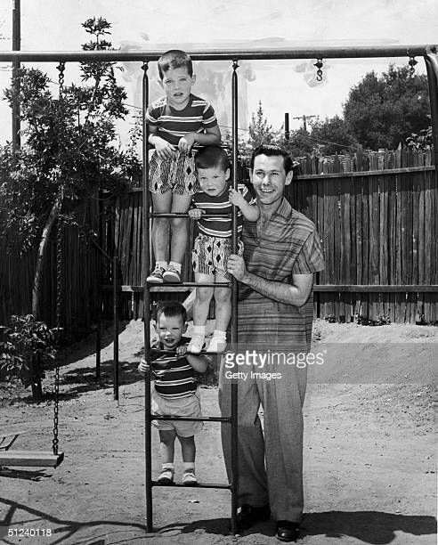 Circa 1955 American television host Johnny Carson poses with his three sons top to bottom Kit Ricky and Corey on a ladder in their back yard at home...