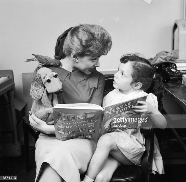 American television personality Shari Lewis reads the tale of Yertle the Turtle to a young girl
