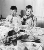 Amid the debris of a Thanksgiving meal two young boys chew on turkey legs