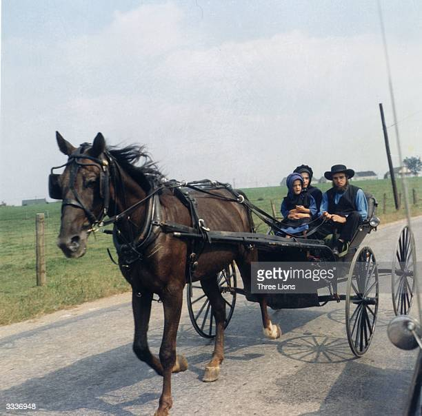 An Amish family rides to town in an open buggy The Amish have maintained a conservative agricultural way of life eschewing modern industrial society