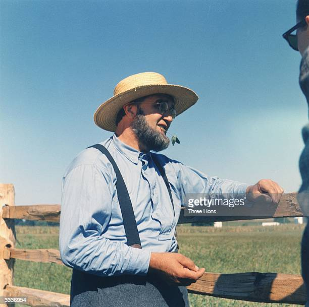 An Amish farmer looks over his fields The Amish have maintained a conservative agricultural way of life eschewing modern industrial society