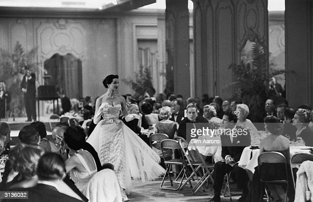 An evening dress being modelled at a fashion show held by Saks of Fifth Avenue New York The audience who are in evening dress are also being wined...