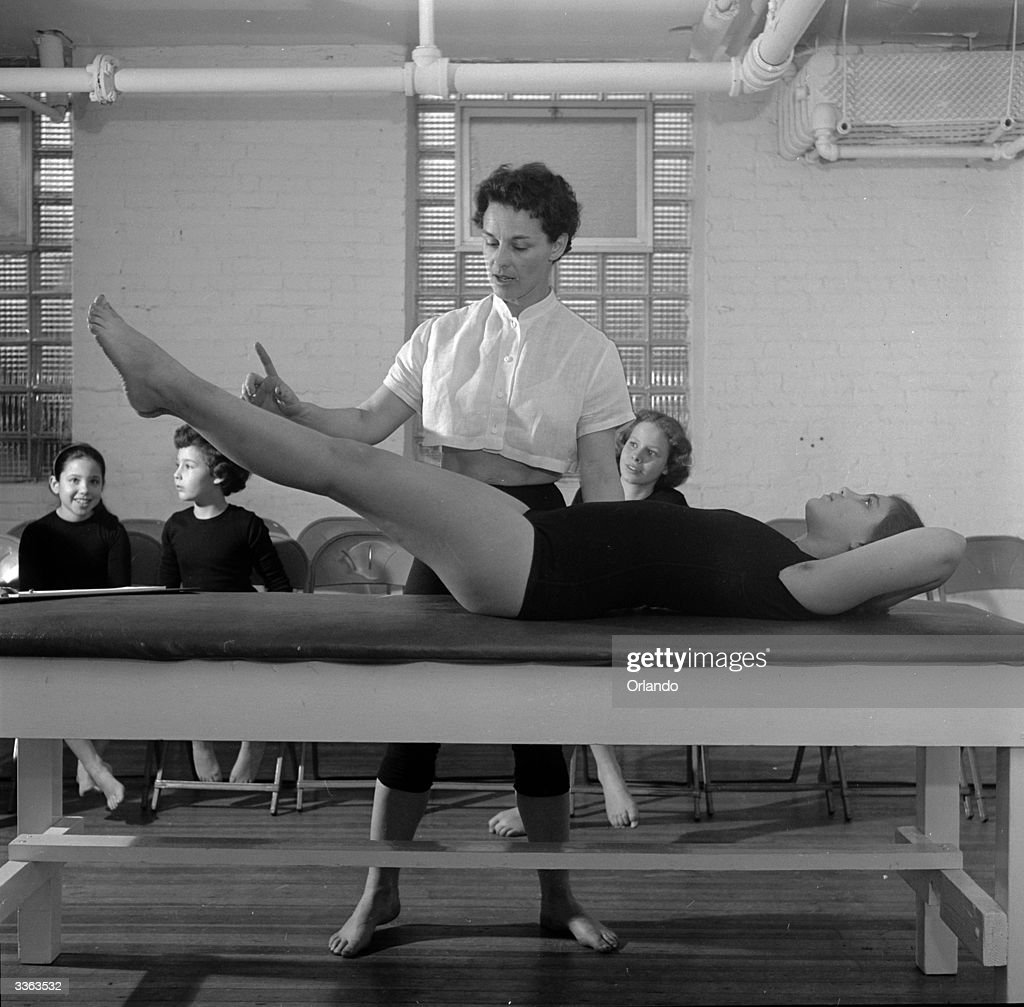 Bonnie Prudden, Director of the Institute of Physical Fitness, White Plains, New York helps a student in the third Kraus_Weber test. In this a person must slowly raise their legs from the supine position.
