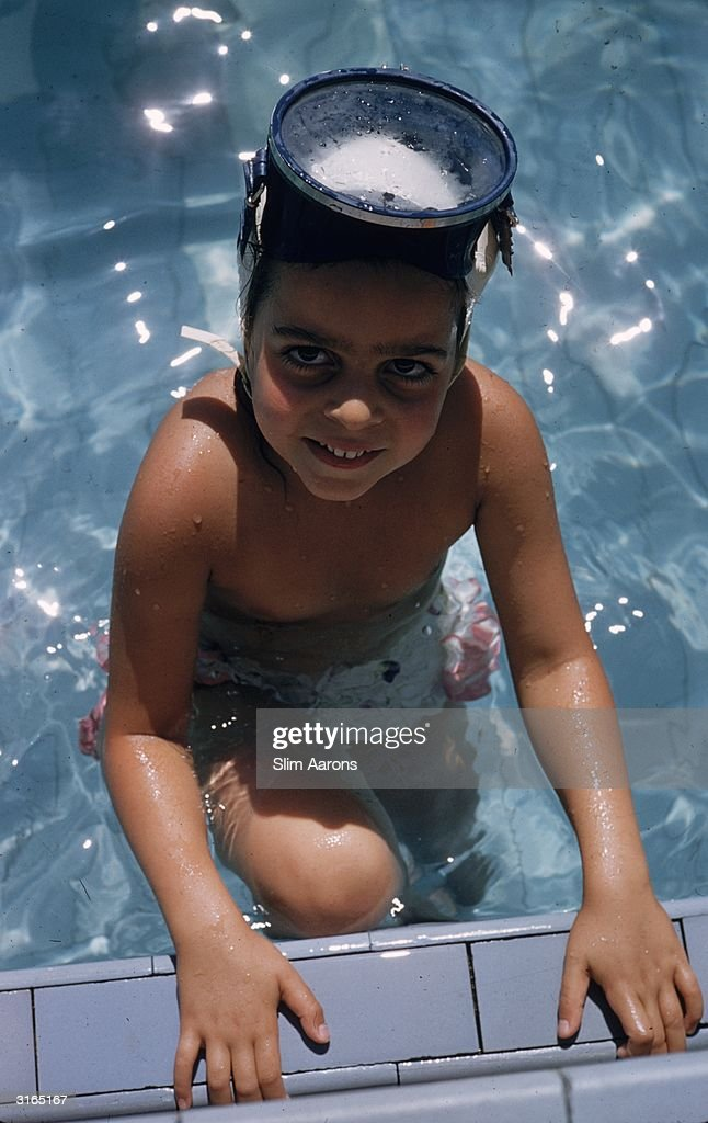 Christina Onassis, the daughter of Greek shipping tycoon Aristotle Onassis, climbing out of a swimming pool wearing a snorkel mask on her head.