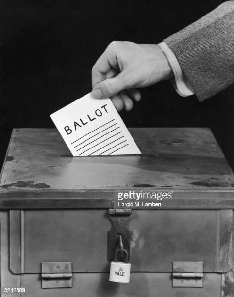 Closeup of a man's hand preparing to drop a ballot through the slot of a padlocked ballot box