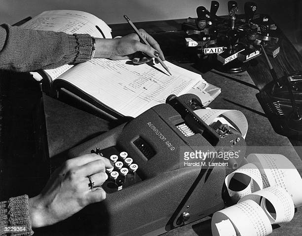 Closeup of the hands of a female accountant using a Remington Rand adding machine while writing in a ledger with a pencil Receipt paper spirals out...