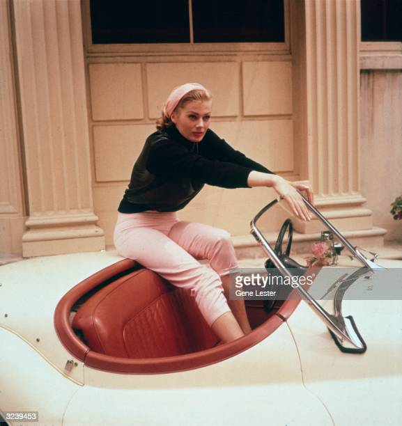 EXCLUSIVE A portrait of Swedish actor Anita Ekberg sitting on the trunk of a cream convertible with her feet in its red leather interior Hollywood...