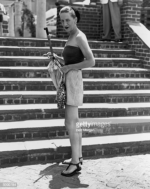 EXCLUSIVE American fashion editor Diana Vreeland wearing a tube top and mini skirt holding a leopard print purse umbrella and a cigarette Southampton...