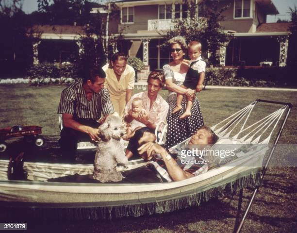 EXCLUSIVE American filmmaker and producer Walt Disney relaxing on a hammock with his family and their pet dog California Pictured are Disney's wife...