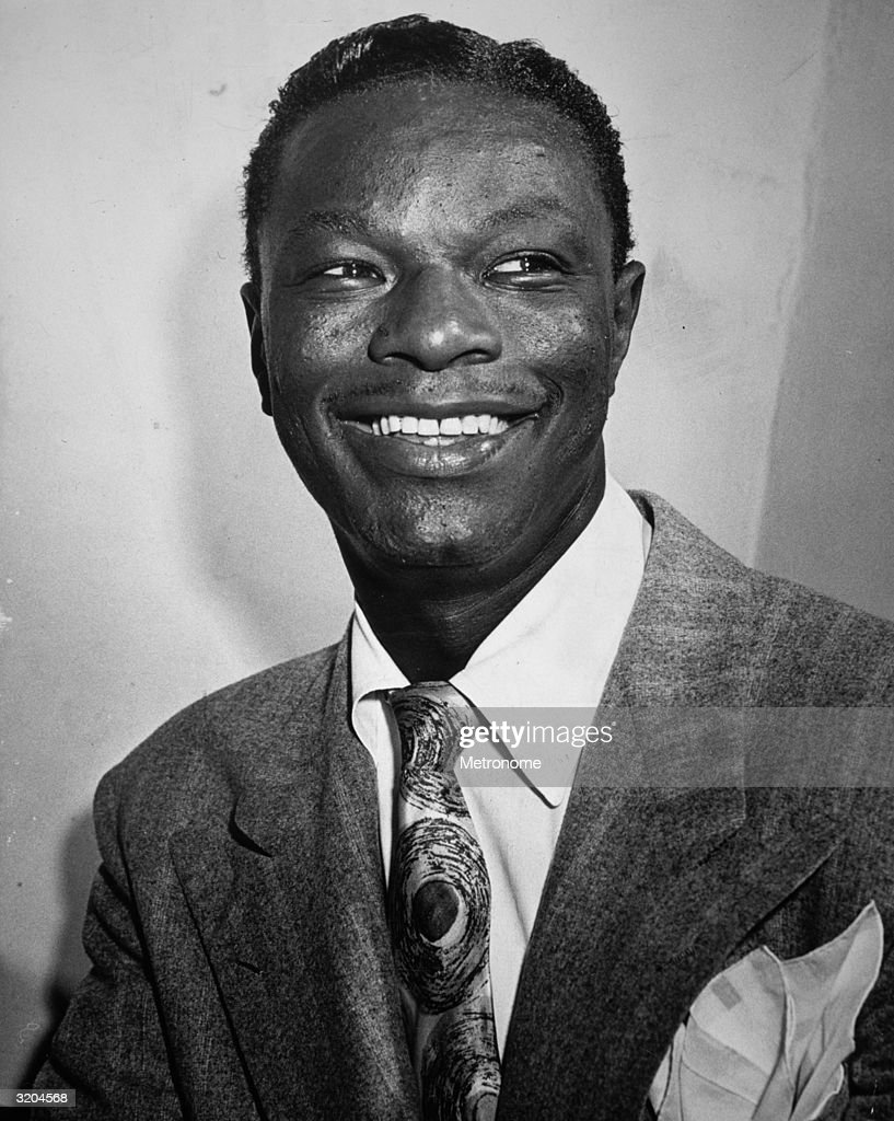 Headshot of jazz musician <a gi-track='captionPersonalityLinkClicked' href=/galleries/search?phrase=Nat+King+Cole&family=editorial&specificpeople=217991 ng-click='$event.stopPropagation()'>Nat King Cole</a> (1919 - 1965) smiling.
