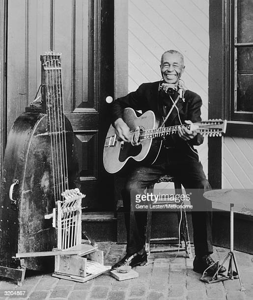 EXCLUSIVE Promotional portrait of American 'oneman band' folk and blues musician Jesse Fuller sitting on a porch and playing the acoustic guitar...