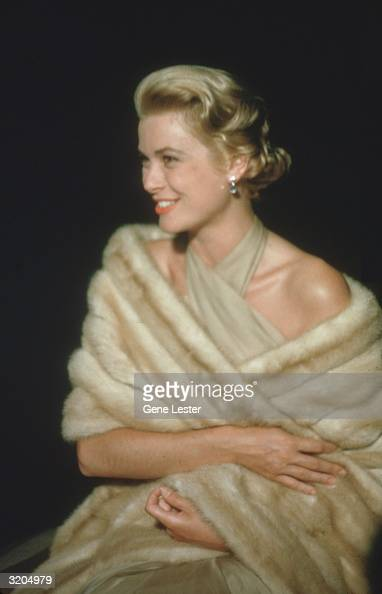 EXCLUSIVE Studio portrait of American actor Grace Kelly laughing while sitting in a beige halter dress and a caramelcolored fur wrap which hangs to...