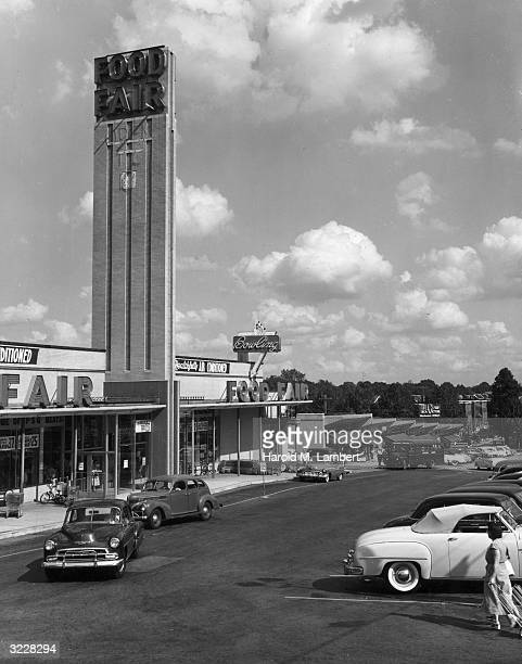 Exterior view of a Food Fair supermarket and its parking lot in a strip mall 1950s