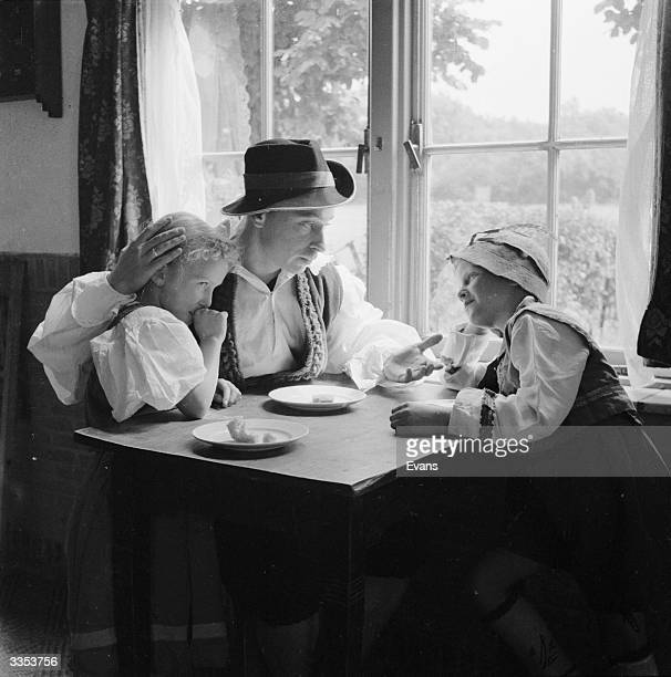 Fairy tale characters Hansel and Gretel sharing their last loaf of bread at the table with their father