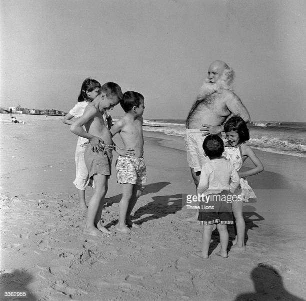 Father Christmas lookalike Lucky Squire exercising on the beach with a group of admiring children