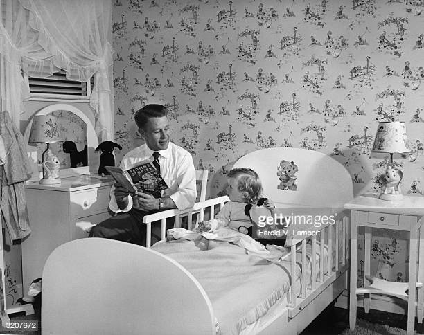 Father reading from 'Bedtime Stories' to a young girl in bed