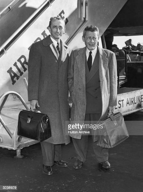 French oceanographer Jacques Yves Cousteau and French polar explorer Paul Victor pose in front of an Air France ramp after arriving in New York City...