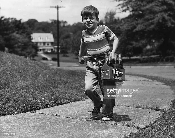 Fulllength image of a young boy walking on the sidewalk carrying a sixpack of bottled Hires root beer