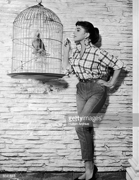 Fulllength portrait of Britishborn actor Joan Collins feeding a parrot in a birdcage a cracker Collins is wearing jeans and a plaid shirt with the...