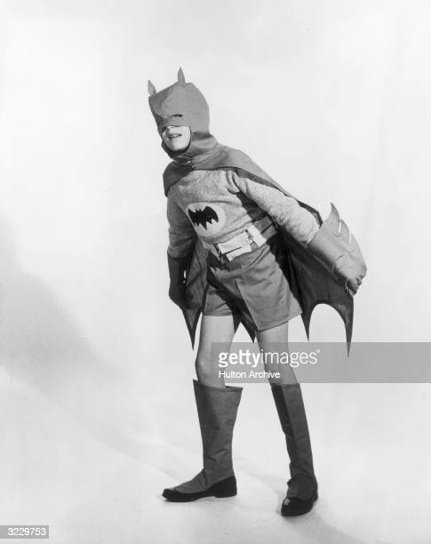Fulllength studio portrait of a boy wearing a Batman comic book hero costume 1950s