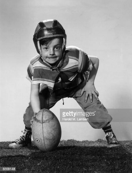 Fulllength studio portrait of a young boy wearing a leather helmet a torn Tshirt and shoulder pads preparing to hike a football