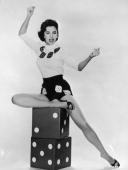 Fulllength studio portrait of American actor and dancer Cyd Charisse sitting on top of large stacked dice and snapping her fingers in the air...