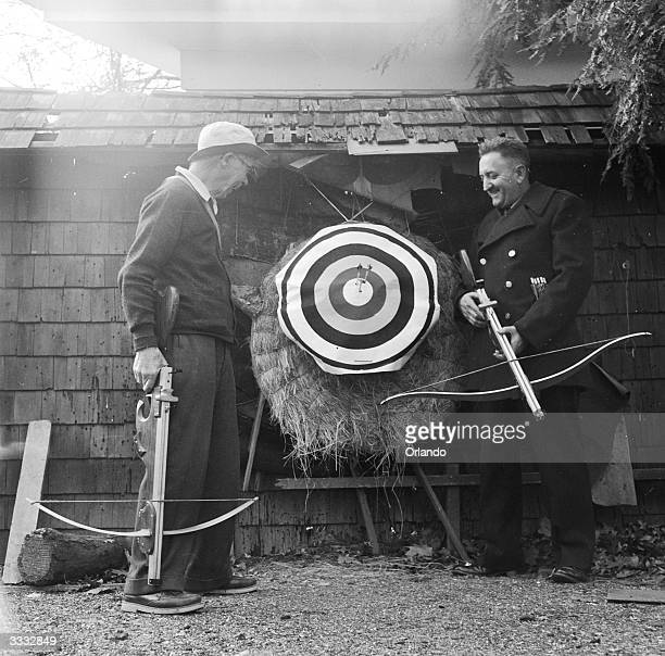 Harry L Bailey of Elizabeth New Jersey inventor of the modern crossbow admires the marxmanship of national champion Paul Eytel