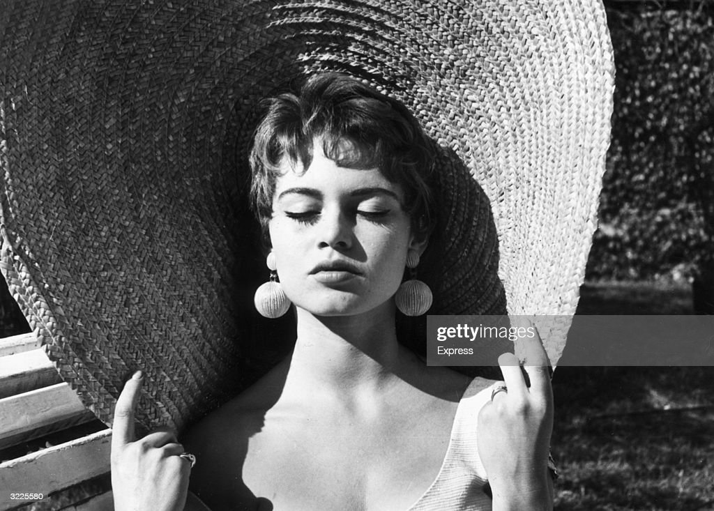 Headshot of French actor Brigitte Bardot closing her eyes and holding the rim of her straw hat while basking in the sun outdoors. Bardot has brunette hair and wears drop earrings.