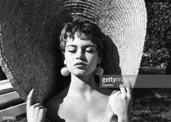 Headshot of French actor Brigitte Bardot closing her eyes and holding the rim of her straw hat while basking in the sun outdoors Bardot has brunette...
