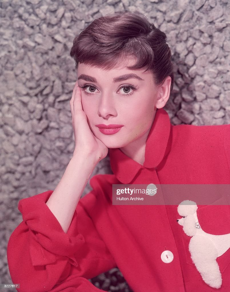 Headshot portrait of Belgian-born actor <a gi-track='captionPersonalityLinkClicked' href=/galleries/search?phrase=Audrey+Hepburn&family=editorial&specificpeople=86470 ng-click='$event.stopPropagation()'>Audrey Hepburn</a> (1929 - 1993) leaning on her hand in a red jacket with a poodle applique.