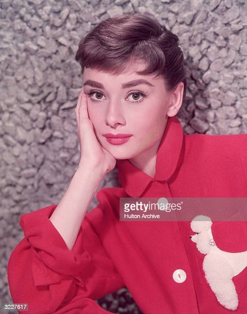 Headshot portrait of Belgianborn actor Audrey Hepburn leaning on her hand in a red jacket with a poodle applique