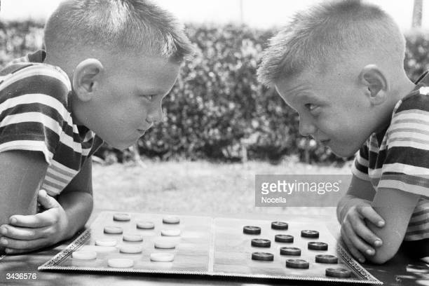 Identical twins Bobby and Jerry psych up for a game of checkers
